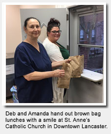 Deb and Amanda hand out brown bag lunches with a smile at St. Anne's Church.