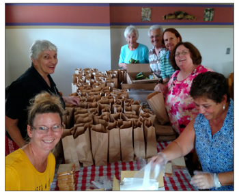 Employees pack lunches for people in need in the community