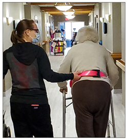 Nurse walks with Resident in hallway