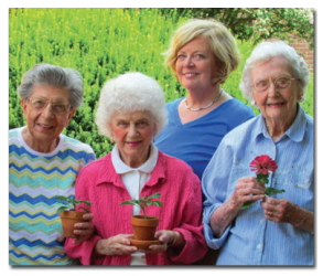 Residents of St. Anne's smile with potted flowers from the garden.