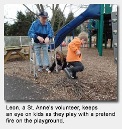 Leon, another St. Anne's volunteer, keeps an eye on kids as they play with a pretend fire on the playground.