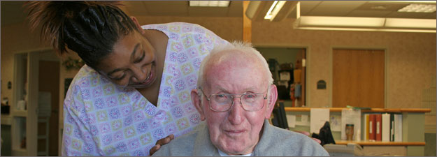 Nurse with her hands on the shoulders of senior Resident in her care.