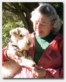 St. Anne's Resident holding dog with scarf.